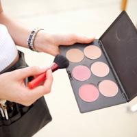 makeup artist holding a makeup palette